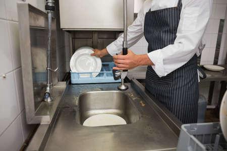 lavar: Porter cocina platos en el fregadero de limpieza en una cocina comercial
