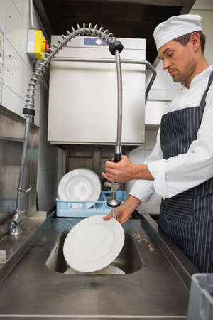 porter: Kitchen porter cleaning plates in sink in a commercial kitchen LANG_EVOIMAGES