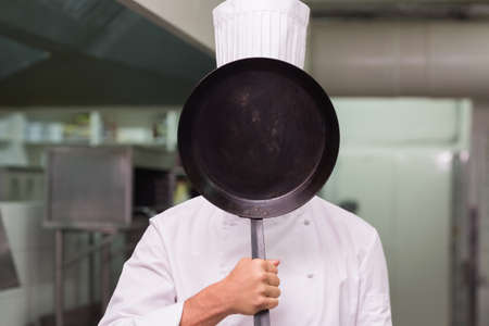 covering face: Chef covering face with pan in a commercial kitchen