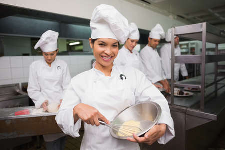 whisking: Happy chef whisking bowl of eggs smiling at camera in a commercial kitchen