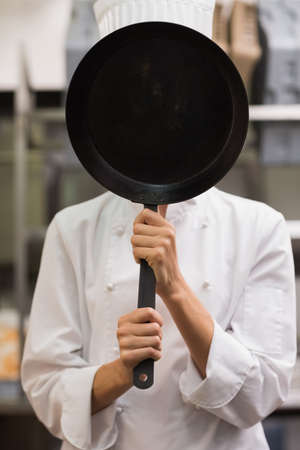 covering face: Chef standing covering face with frying pan in a commercial kitchen