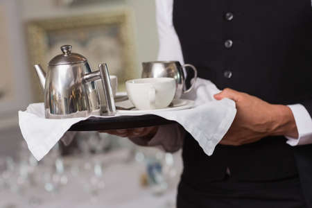 stand teapot: Waiter holding tray with afternoon tea in a fancy restaurant