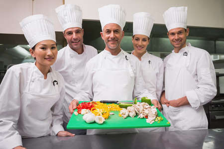 trainees: Head chef showing board of vegetables with trainees in a commercial kitchen