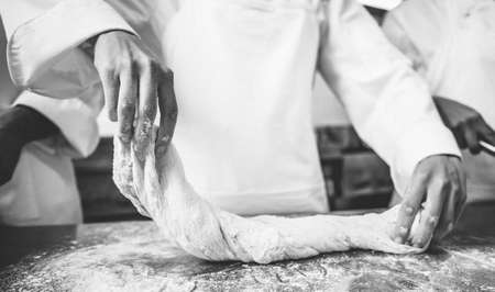 commercial kitchen: Chefs preparing dough at counter in a commercial kitchen LANG_EVOIMAGES
