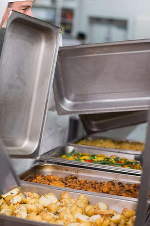 lids: Chefs lifting lids from serving trays in a commercial kitchen