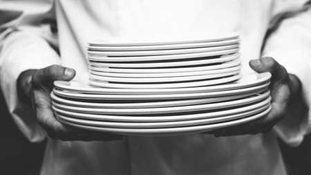 commercial kitchen: Chef holding stack of plates in a commercial kitchen