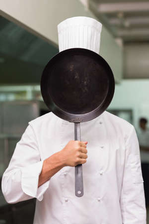 covering the face: Chef covering face with pan in a commercial kitchen