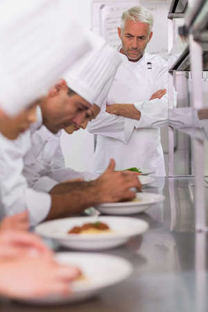 basil  leaf: Head chef watching row of chefs garnishing spaghetti dishes with basil leaf in a commercial kitchen LANG_EVOIMAGES