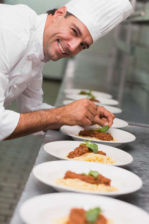 basil  leaf: Happy chef putting basil leaf on spaghetti dish in a commercial kitchen LANG_EVOIMAGES