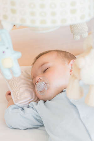 babygro: Baby boy sleeping in crib at home in bedroom LANG_EVOIMAGES