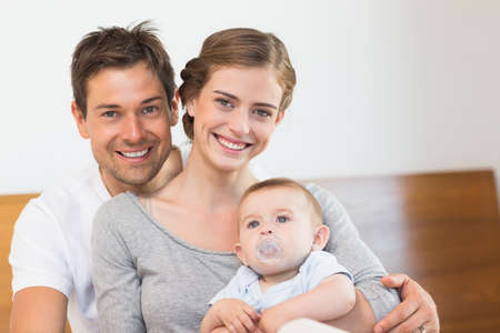 babygro: Happy parents with their cute baby son at home in bedroom LANG_EVOIMAGES