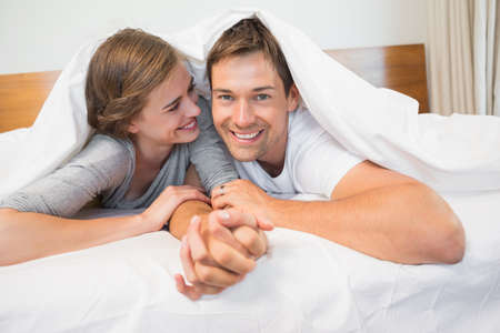 duvet: Happy couple under the duvet at home in bedroom LANG_EVOIMAGES