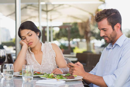 bored woman: Bored woman being ignored by her date in patio of restaurant