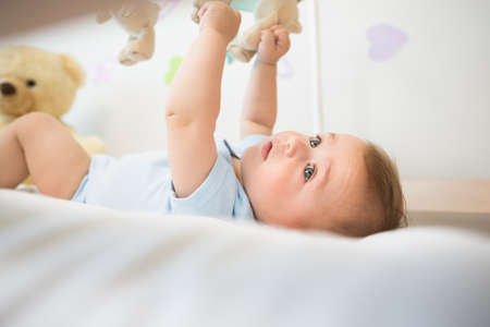 babygro: Baby boy lying in crib playing with mobile at home in bedroom