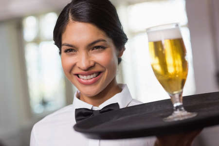 tied hair: Pretty waitress holding tray with glass of beer in a fancy restaurant
