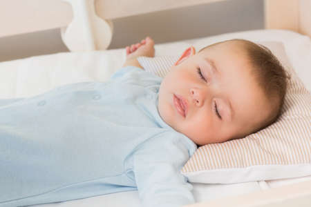 domicile: Baby boy sleeping in crib at home in bedroom LANG_EVOIMAGES