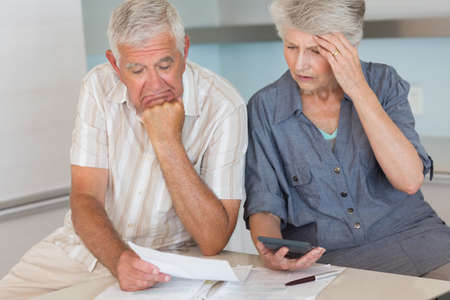 credit crunch: Worried senior couple organising their finances at home in the kitchen