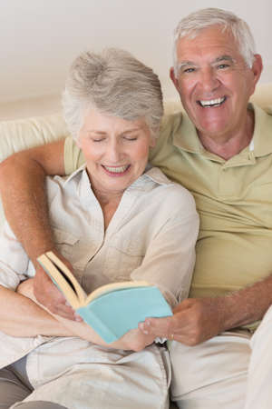 couple on couch: Senior couple sitting on couch reading together at home in the living room