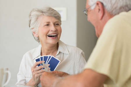 senior adults: Happy senior couple playing a card game at home in the kitchen LANG_EVOIMAGES