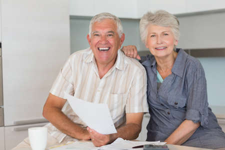figuring: Happy senior couple organising their finances at home in the kitchen LANG_EVOIMAGES