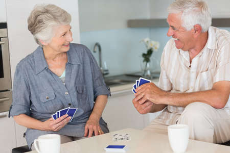 jeu de cartes: Happy senior couple playing a card game at home in the kitchen LANG_EVOIMAGES