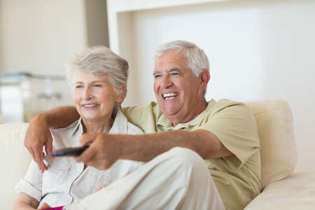 changing channel: Happy senior couple watching tv on the couch at home in the living room