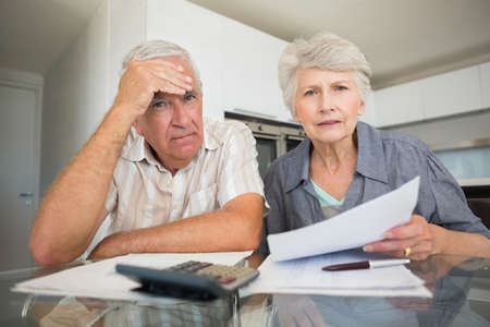 figuring: Worried couple paying their bills looking at camera at home in the kitchen