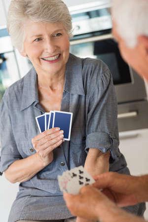 jeu de carte: Couple de personnes �g�es heureux de jouer un jeu de cartes � la maison dans la cuisine