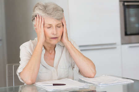 figuring: Worried senior woman paying her bills at home in the kitchen