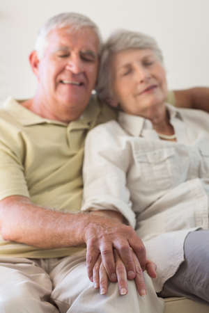 couple on couch: Senior couple napping on the couch at home in the living room