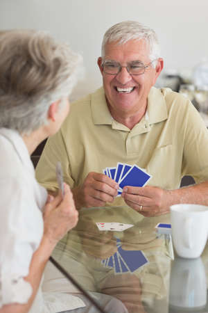 jeu de carte: Happy senior couple playing a card game at home in the kitchen LANG_EVOIMAGES