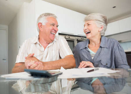 figuring: Happy couple using the calculator to pay bills at home in the kitchen