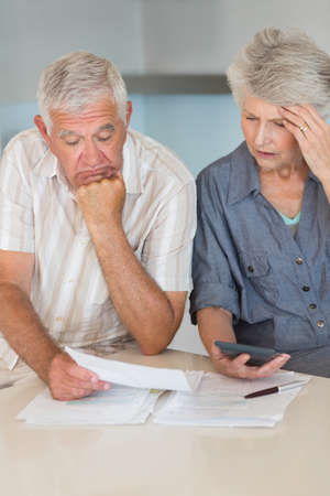 figuring: Worried senior couple organising their finances at home in the kitchen