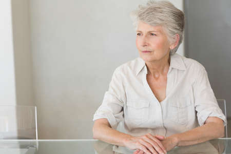 forlorn: Depressed senior woman sitting at the table at home in the kitchen