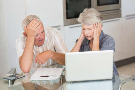 credit crunch: Worried senior couple using the laptop to pay bills at home in the kitchen LANG_EVOIMAGES