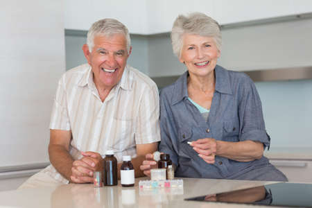 organising: Happy senior couple organising their medicine at home in the kitchen