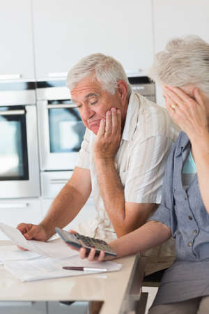 organising: Worried senior couple organising their finances at home in the kitchen