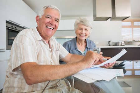 figuring: Happy couple paying their bills at the table at home in the kitchen