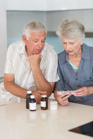 pillbox: Senior couple looking at their medicine at home in the kitchen