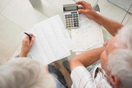 pay bills: Senior couple using the calculator to pay bills at home in the kitchen