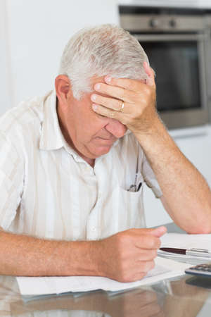 figuring: Worried senior man paying his bills at home in the kitchen