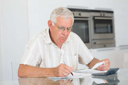 figuring: Focused senior man paying his bills at home in the kitchen LANG_EVOIMAGES