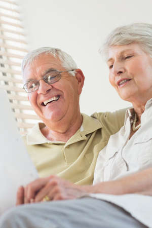 couple on couch: Senior couple looking at document together on the couch at home in the living room LANG_EVOIMAGES