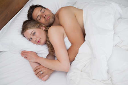 loving couples: High angle view of a loving relaxed young couple together in bed at home
