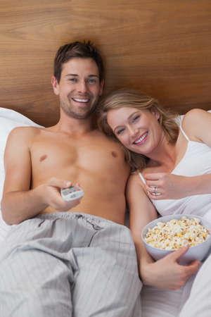 pareja viendo tv: Vista de ángulo alto de una joven pareja amorosa relajada viendo la televisión en la cama en su casa LANG_EVOIMAGES