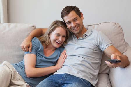 pareja viendo television: joven pareja viendo la televisión en el sofá en la sala de estar en casa