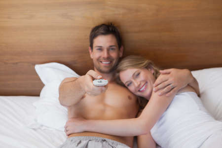 pareja viendo tv: High angle view of a loving relaxed young couple watching tv in bed at home LANG_EVOIMAGES