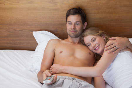 pareja viendo television: Vista de ángulo alto de una joven pareja amorosa relajada viendo la televisión en la cama en su casa LANG_EVOIMAGES