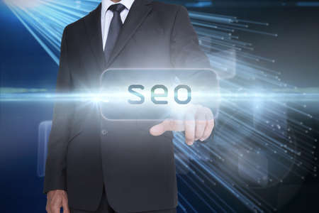 against abstract: The word seo and businessman pointing against abstract technology background LANG_EVOIMAGES
