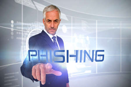 scamming: The word phishing and businessman pointing against futuristic technology interface LANG_EVOIMAGES